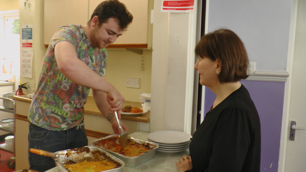 A customer Peer Mentor serves lunch to Maggie Jones, Foundation CEO